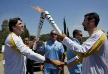 Olympic flame second torch bearer former volleyball player Giovane Gavio from Brazil passes the torch to third bearer Dimitrios Mougios as they attend the Olympic flame lighting ceremony for the Rio 2016 Olympic Games on the site of ancient Olympia